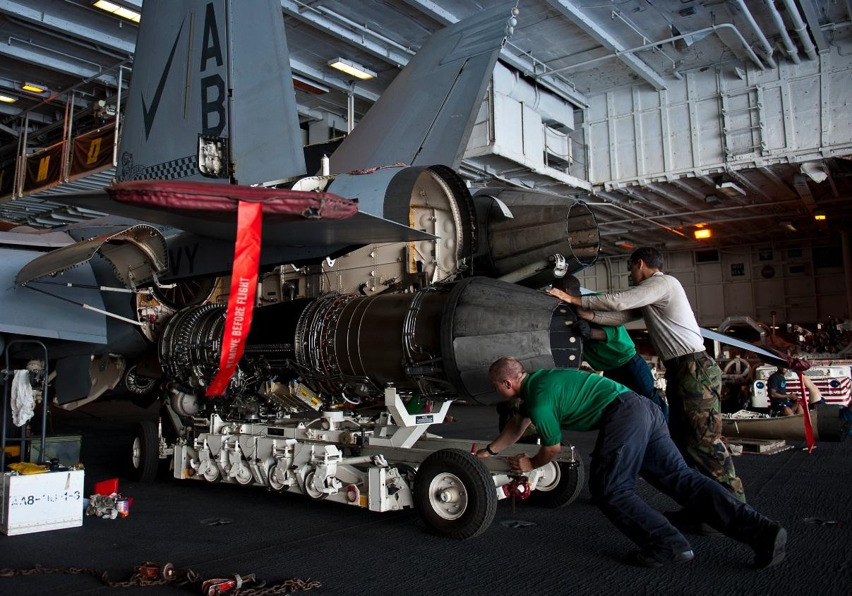 Instalação-de-motor-F414-num-F-18-F-Super-Hornet-no-hangar-do-porta-aviões-Enterprise-foto-Marinha-dos-EUA