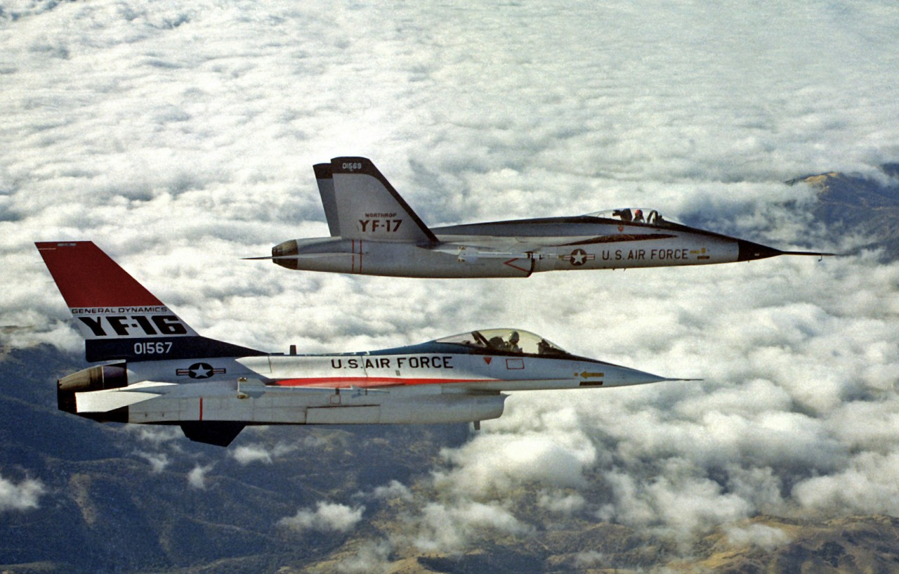 An air-to-air right side view of a YF-16 aircraft and a YF-17 aircraft, side-by-side, armed with AIM-9 Sidewinder missiles.
