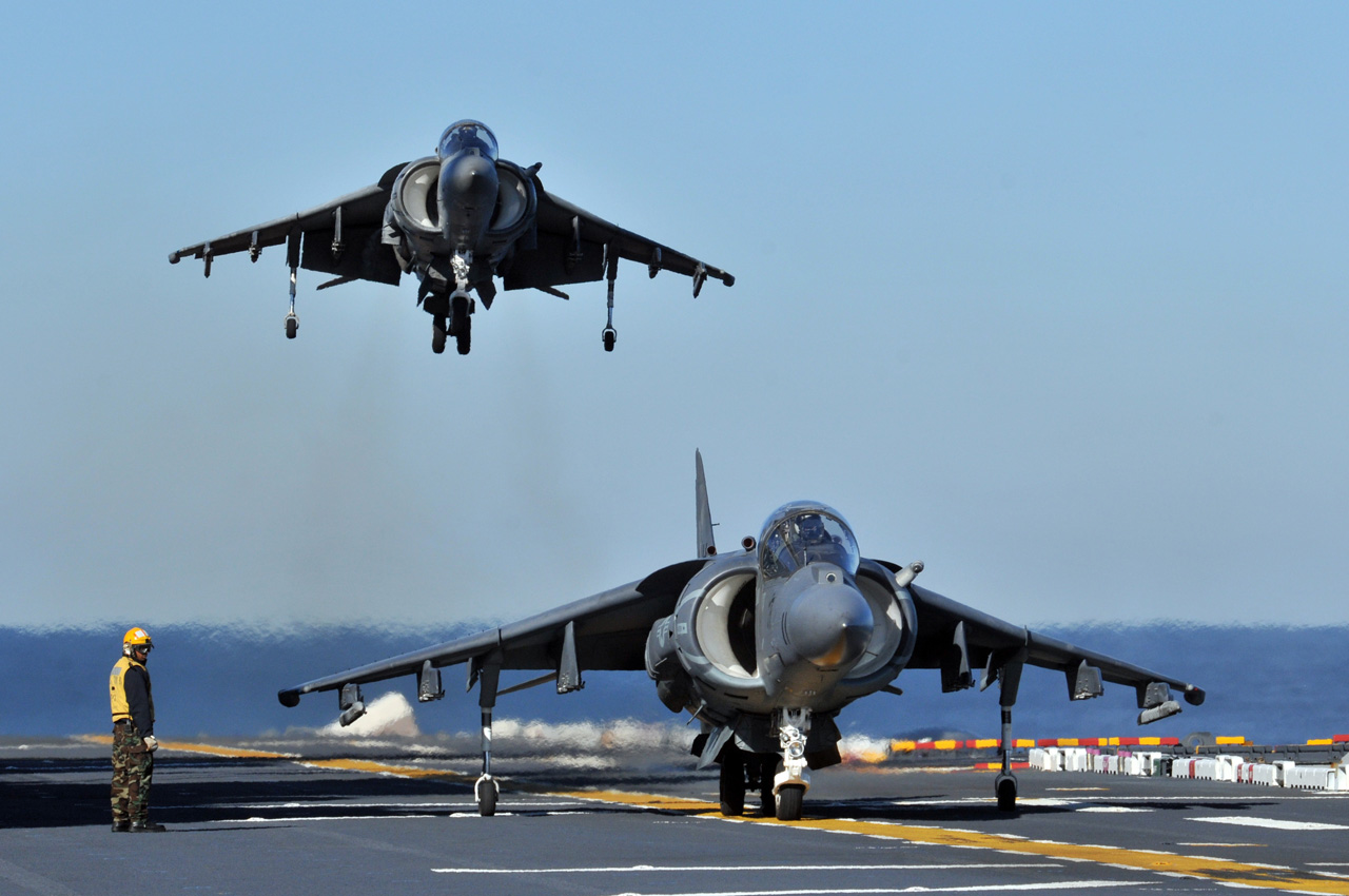 Two AV-8B Harriers from Marine Attack Squadron (VMA) 542 conduct flight operations aboard the amphibious assault ship USS Kearsarge (LHD 3)