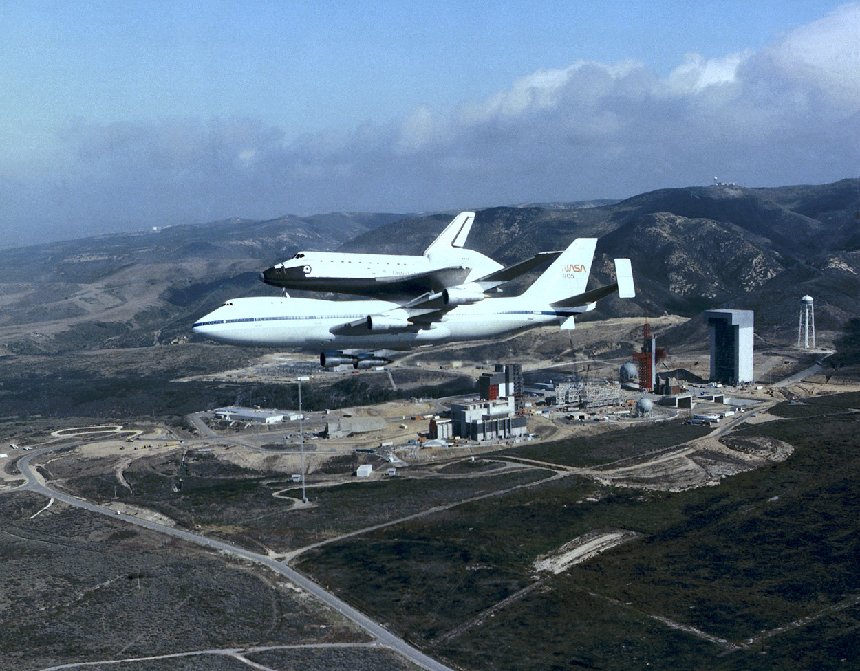 Space Shuttle Discovery, atop Shuttle Carrier Aircraft 905, flies over Vandenberg Air Force Base Space Launch Complex 6 during November 1984