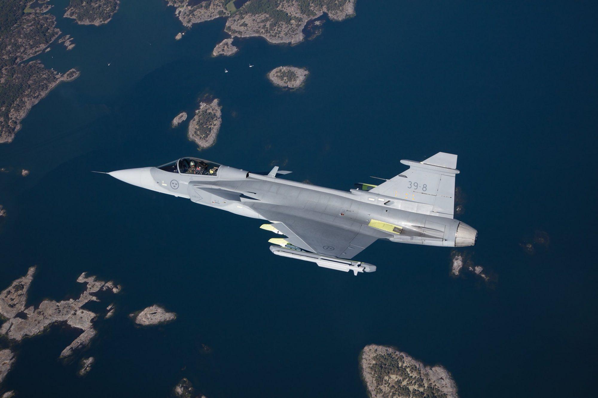 Gripen E voando com mísseis ar-ar IRIS-T na posta das asas