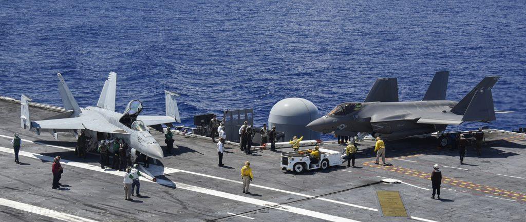 Um F/A-18E Super Hornet e um F-35C Lightning II a bordo do porta-aviões USS Abraham Lincoln (CVN 72). Foto: Marinha dos EUA