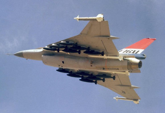 An air to air left underside view of an F-16XL aircraft. The aircraft is armed with two wing tip mounted AIM-9 Sidewinder and four fuselage mounted AIM-7 Sparrow missiles along with 12 500-pound bombs.